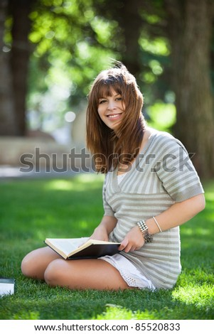 Portrait of college student sitting on campus lawn - stock photo