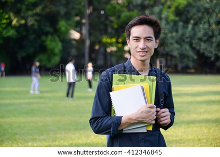 Portrait of college student standing holding book at his university