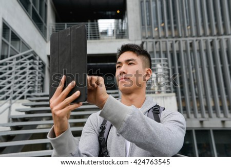 Portrait of college student use tablet in her hand at campus
