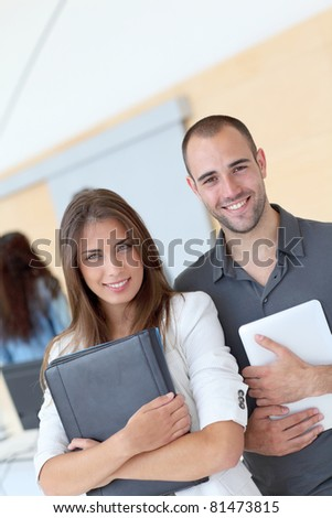 Portrait of college students standing in college hall - stock photo