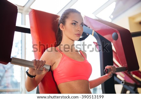 Portrait of concentrated beautiful young woman athlete training in gym  - stock photo