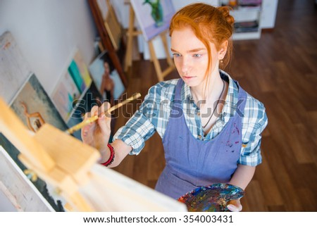 Portrait of concentrated beautiful young woman painter holding art palette and painting on canvas with brush in artist workshop - stock photo