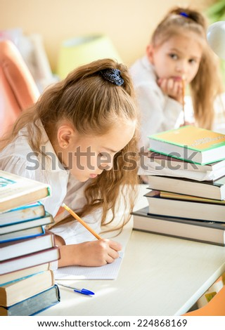 Portrait of concentrated girl doing homework while classmate trying to write off - stock photo
