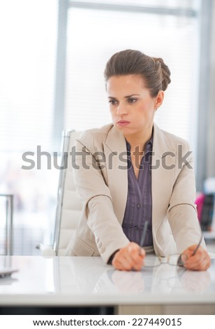 Portrait of concerned business woman with eyeglasses in office - stock photo