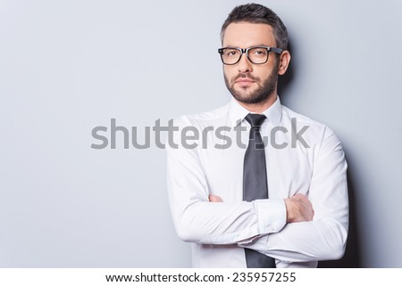 Portrait of confidence and success. Portrait of handsome mature man in shirt and tie keeping arms crossed and looking at camera while standing against grey background - stock photo