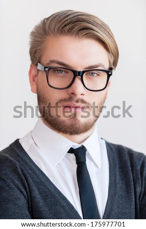 Portrait of confidence. Portrait of handsome young man in glasses looking at camera while standing against grey background