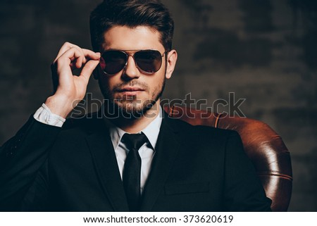 Portrait of confidence.Portrait of young handsome man in suit adjusting his sunglasses and looking at camera while sitting in leather chair against dark grey background - stock photo