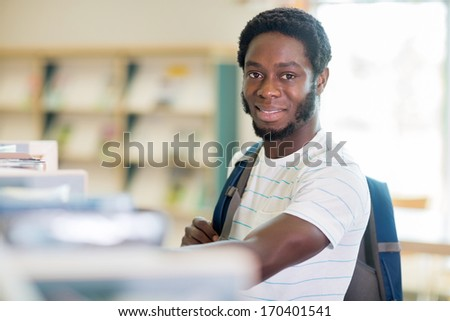 Portrait of confident African American student with carrying backpack in library