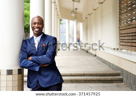 Portrait of confident african businessman standing outdoors with his arms crossed - stock photo