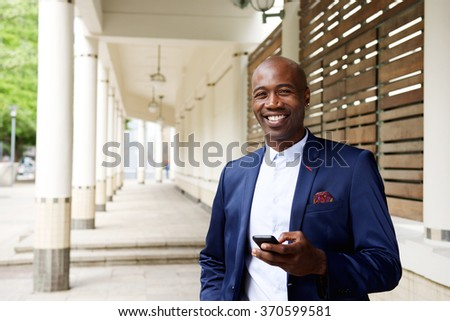 Portrait of confident african businessman with a mobile phone standing outdoors - stock photo