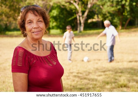 Portrait of confident and happy grandmother, smiling at camera while her grandson and husband play football in background. Concept of grandparents spending time with boys. - stock photo