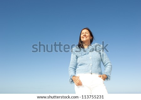 Portrait of confident and happy relaxed looking attractive senior woman enjoying active retirement in winter sun, isolated with blue sky as background and copy space. - stock photo