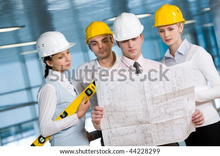 Portrait of confident architects in helmets learning blueprint - stock photo