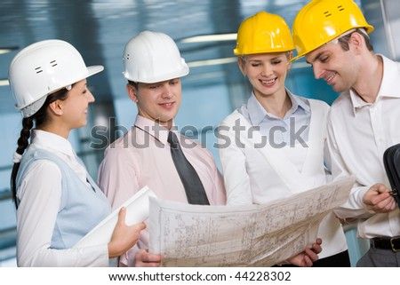 Portrait of confident architects in helmets planning their work - stock photo