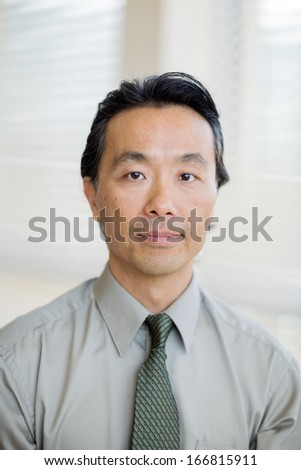 Portrait of confident Asian cancer specialist in shirt and tie at hospital - stock photo