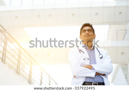 Portrait of confident Asian Indian medical doctor standing outside hospital building, beautiful golden sunlight at background. - stock photo
