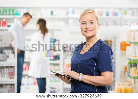 Portrait of confident assistant holding tablet computer while pharmacist and customer standing in background at pharmacy - stock photo