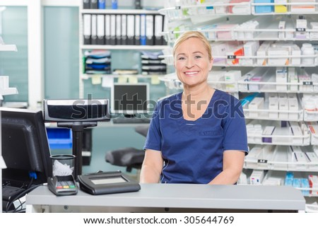 Portrait of confident assistant sitting at cash counter in pharmacy - stock photo