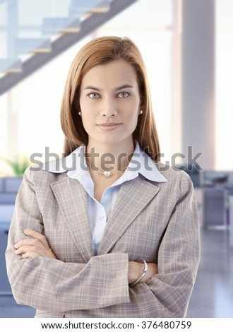 Portrait of confident attractive caucasian female business office worker. Standing, looking at camera, smiling, arms crossed, woman suit. - stock photo
