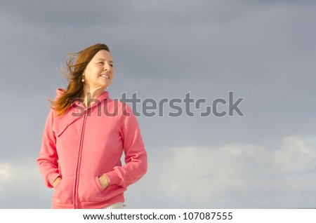 Portrait of confident attractive looking mature woman in pink sweater, at beach, isolated with storm clouds as background and copy space. - stock photo