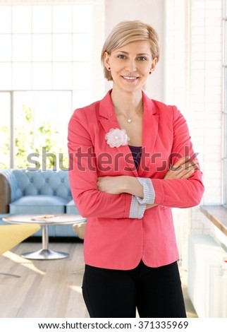 Portrait of confident blonde businesswoman smiling arms crossed. - stock photo