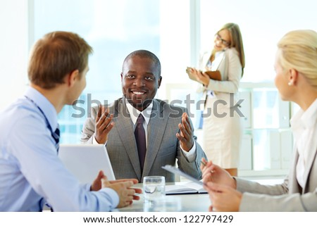 Portrait of confident boss interacting with his partners at meeting - stock photo