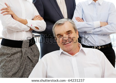 Portrait of confident boss looking at camera with employees behind - stock photo