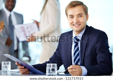 Portrait of confident boss looking at camera with his partners interacting on background