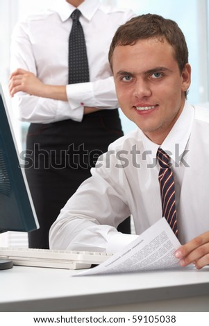 Portrait of confident boss sitting at workplace in office and looking at camera - stock photo