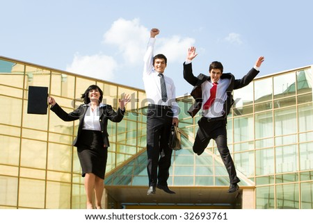 Portrait of confident business group jumping and laughing outdoors