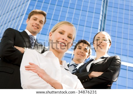 Portrait of confident business group looking at camera with pretty blonde at foreground - stock photo