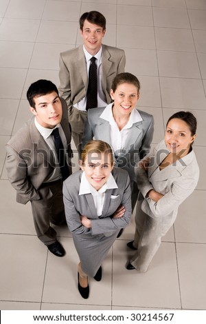 Portrait of confident business group standing on the floor and looking at camera with smiles - stock photo