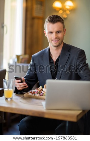 Portrait of confident business man with mobilephone and laptop sitting in restaurant - stock photo