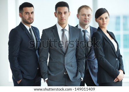 Portrait of confident business partners looking at camera with male leader in front - stock photo