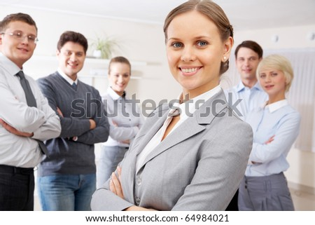 Portrait of confident business people looking at camera with pretty woman in front - stock photo