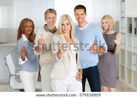 Portrait of confident business people showing thumbs up sign in office - stock photo