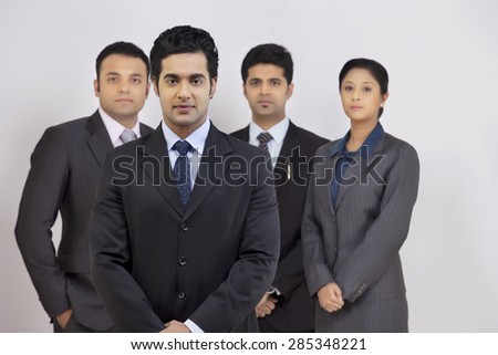 Portrait of confident business people standing against gray background - stock photo