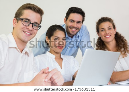 Portrait of confident business people with laptop at desk in office - stock photo
