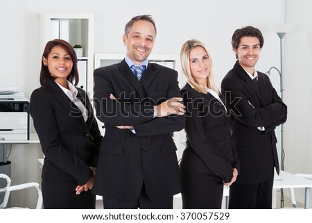 Portrait of confident business team standing together in office