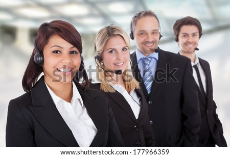 Portrait Of Confident Business Team With Headset Standing In A Line - stock photo