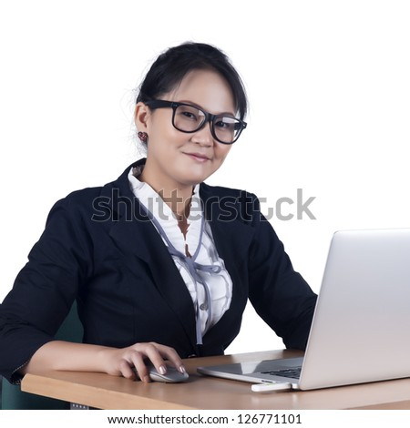 Portrait of confident business woman sitting at the table and working on the laptop, Isolated on white background. Model is Asian woman. - stock photo