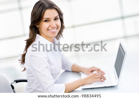 Portrait of confident business woman sitting at the table with laptop