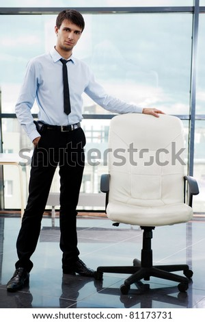 Portrait of confident businessman at his office standing near empty armchair and welcoming new employee. Recruitment concept