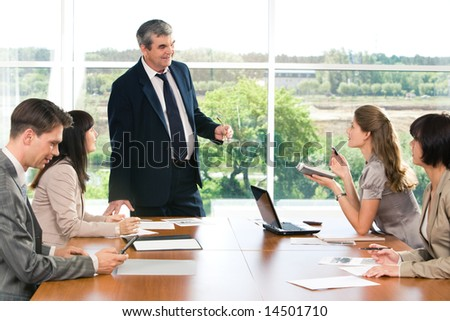 Portrait of confident businessman explaining new business-plan to colleagues at briefing - stock photo