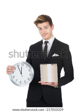 Portrait of confident businessman holding clock and stacked papernotes against white background - stock photo