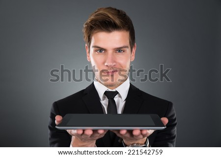 Portrait of confident businessman holding digital tablet over gray background - stock photo