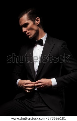 portrait of confident businessman in black suit with bowtie posing seated in dark studio background while closing his jacket and looking away - stock photo