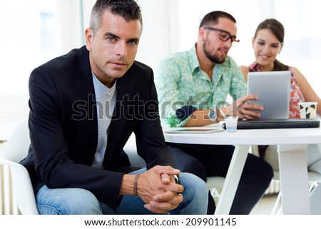 Portrait of confident businessman in office with his team. - stock photo