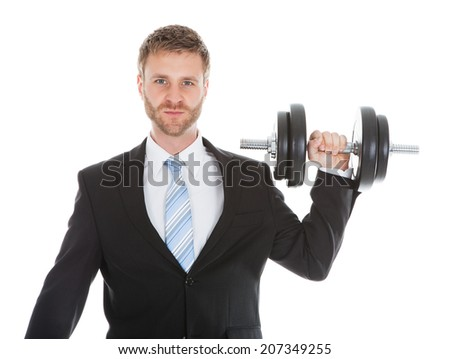 Portrait of confident businessman lifting dumbbell over white background - stock photo