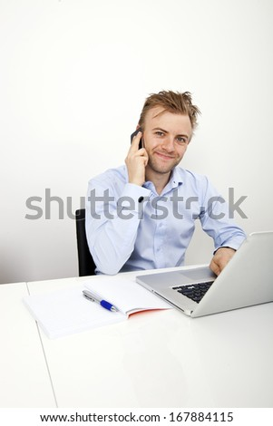 Portrait of confident businessman on call while using laptop in office
